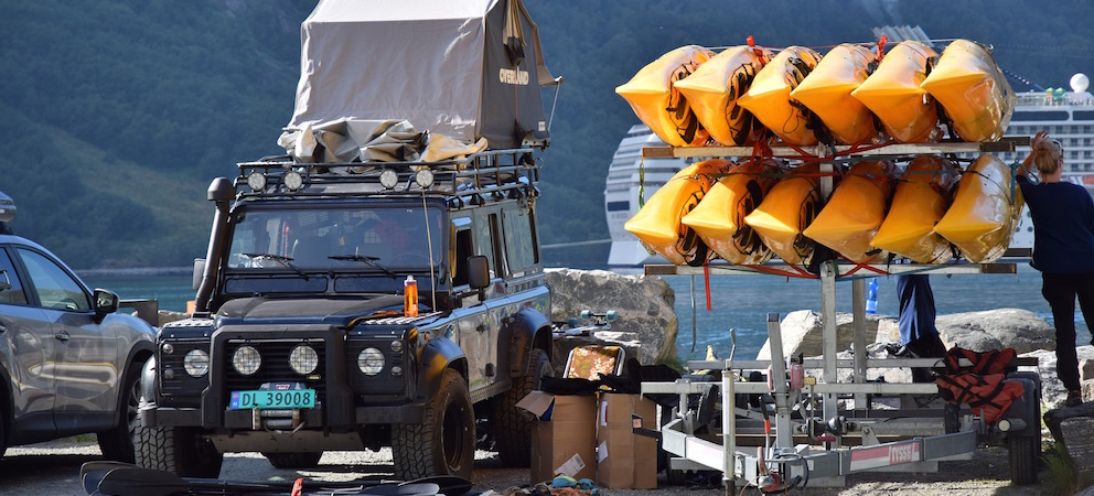 Bug out vehicle Land Rover parked near a lake with water sporting equipment next to kayaks