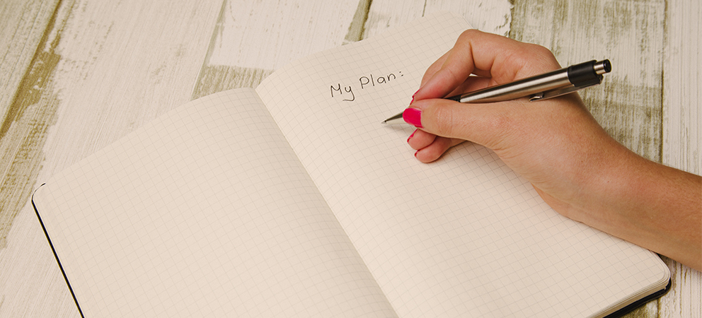 woman writing a survival plan in a notebook