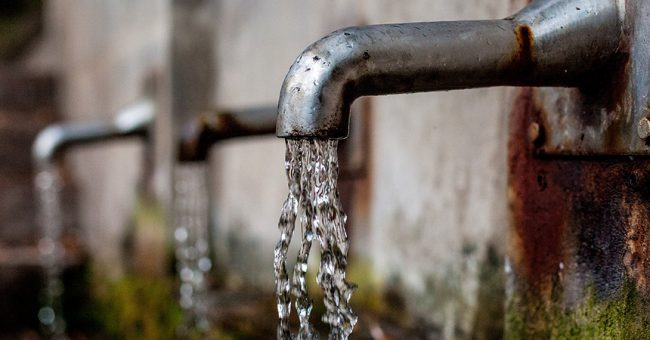 Water flowing from a rusty faucet during a water crisis