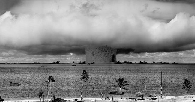 Black and white shot of a nuclear blast going off near a beach