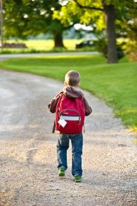 Young boy walking down a dirt road carrying a backpack.