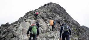 Backpackers wearing bug out backpacks hiking up a mountain