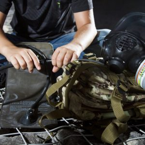 Child connecting MIRA Tactical Gas Mask to CamelBak hydration bladder